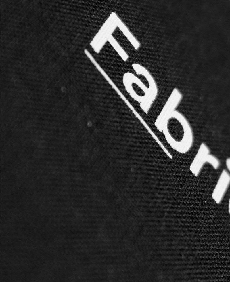 Foto di dettaglio della valigetta che contiene le mazzette in tessuto nero con stampato il nome Fabrics in bianco