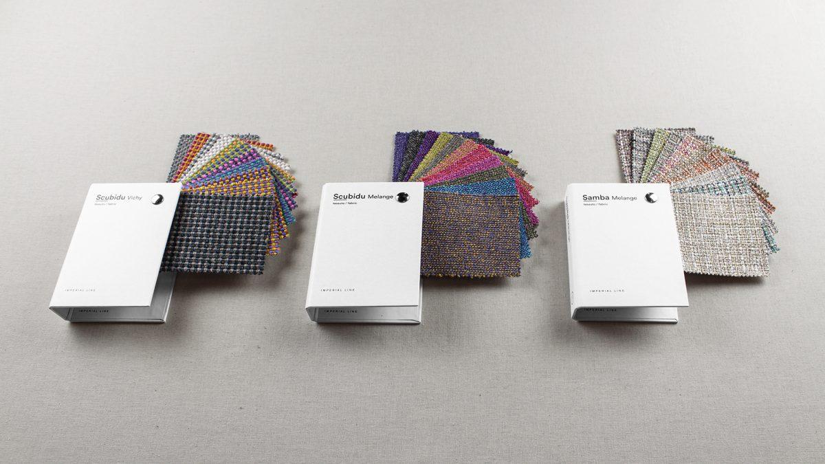 Foto delle tre mazzette Scubidu della collezione Fabrics di Imperial Line con i tessuti che escono a ventaglio