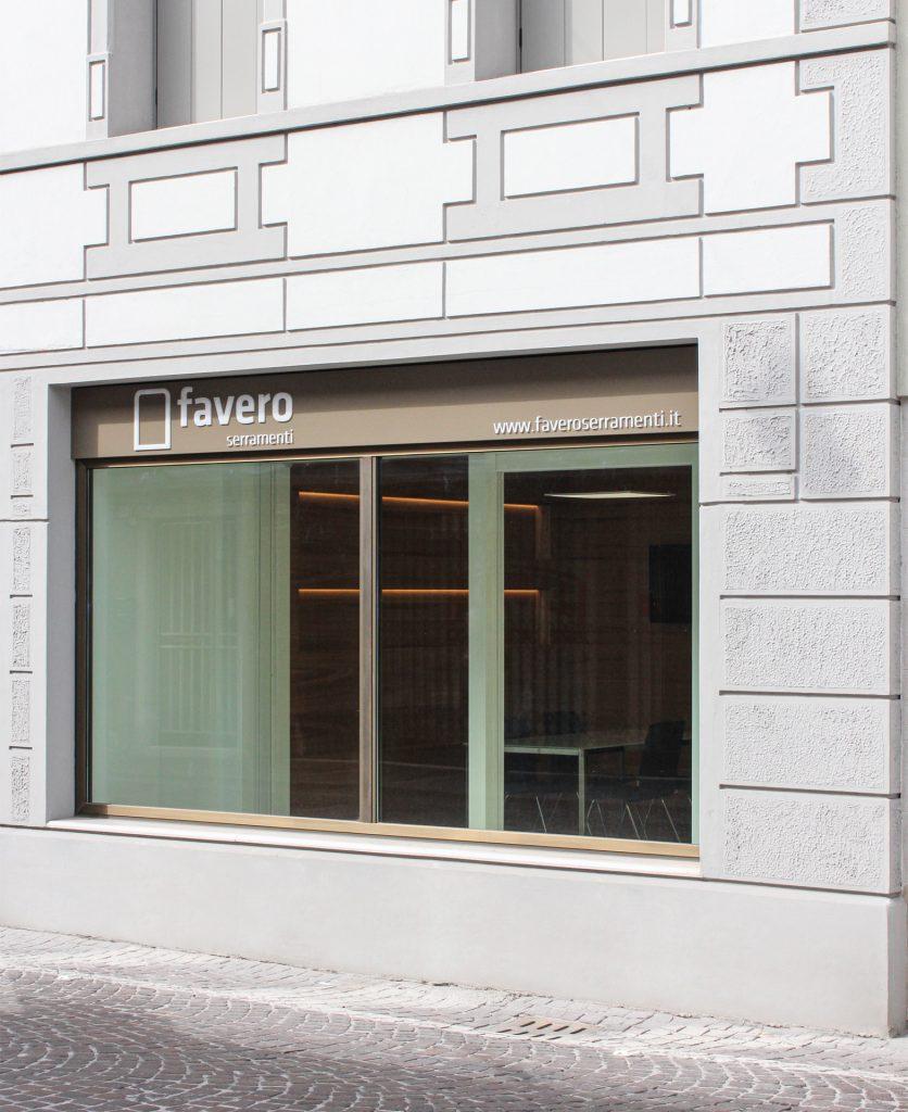 vista di scorcio della vetrina del flagship store con insegna aziendale sulla sommità della vetrata