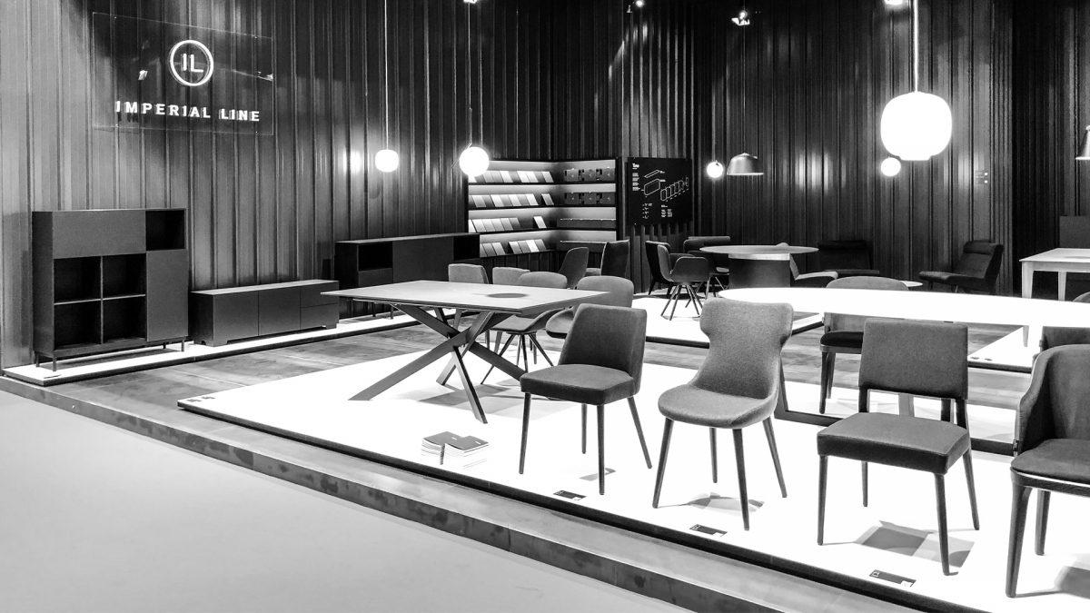 Foto in bianco e nero dello stand con esposti diversi modelli di sedie e tavoli