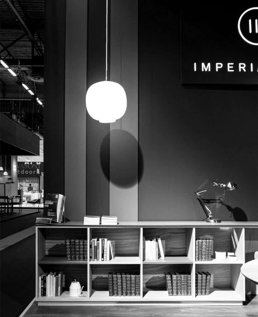 Foto in bianco e nero di una porzione di stand con esposta una madia con all'interno dei libri