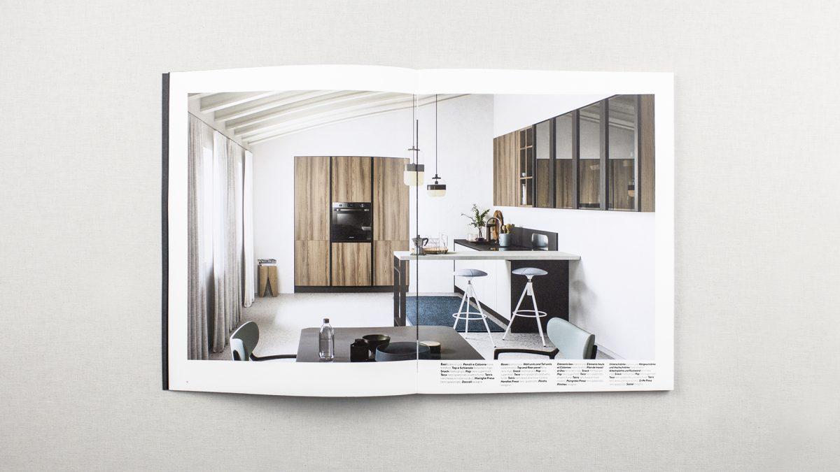 Foto dell'interno del catalogo con il render di una cucina con penisola