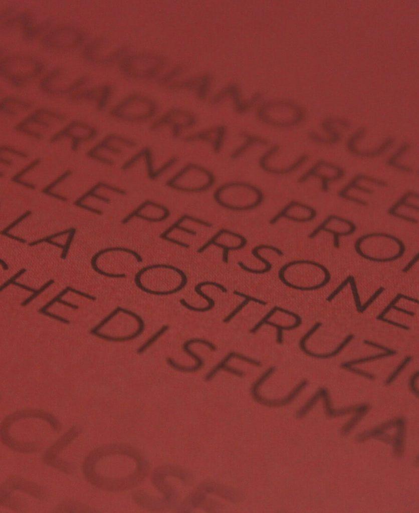 foto di dettaglio di una pagina rossa con testo scritto tono su tono