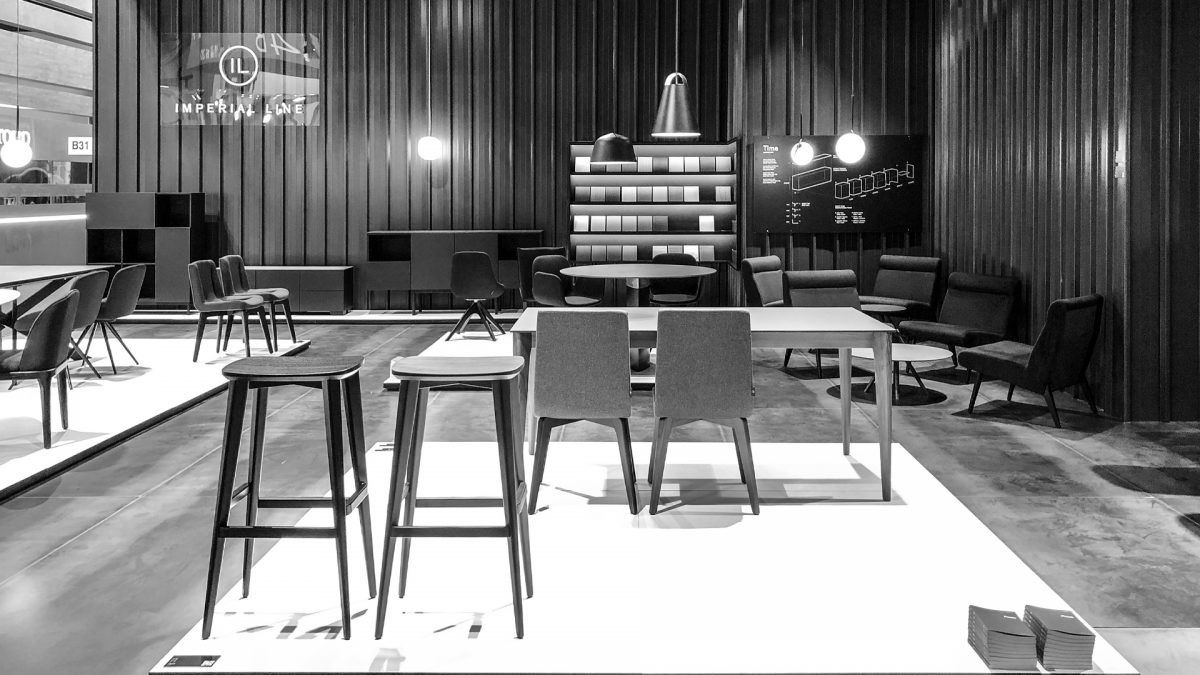 Foto in bianco e nero dello stand con in primo piano due sgabelli e in fondo l'espositore delle finiture e un'infografica dei moduli che compongono le madie