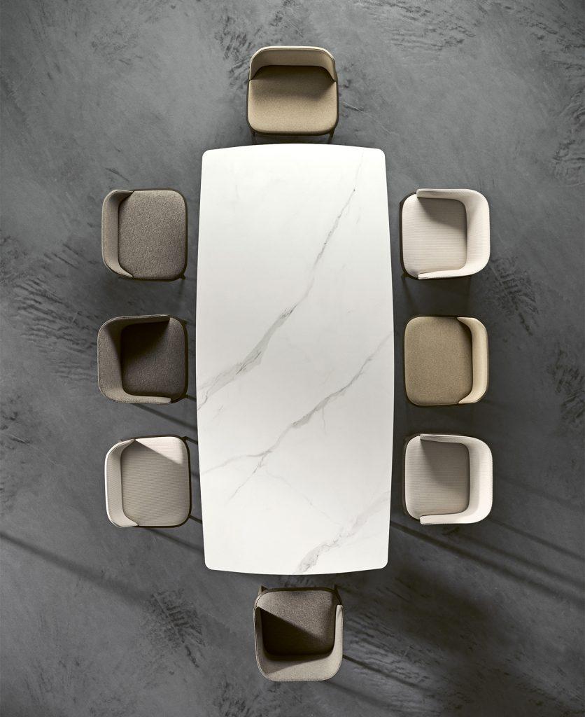 Render zenitale del tavolo Prado con finitura in marmo bianco e con attorno otto sedie Damblé