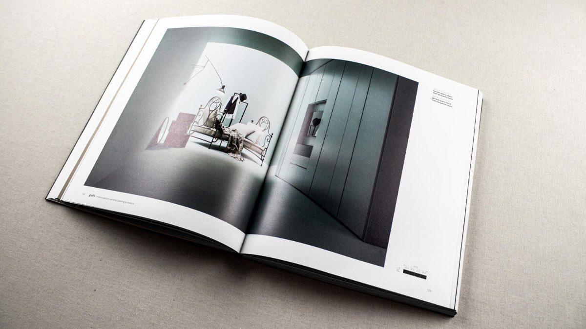 vista di scorcio del catalogo aperto dove si vede l'immagine di un armadio azzurro in un ambiente azzurro