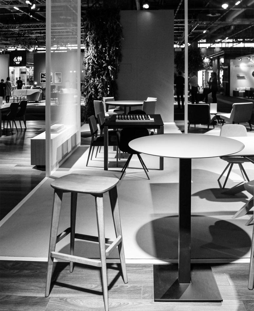 Foto in bianco e nero dei prodotti esposti all'interno dei cubi con sgabello e tavolino in primo piano