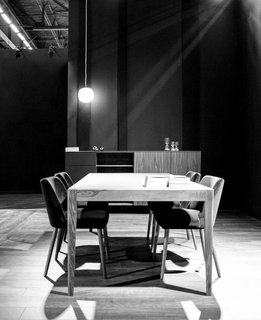 Foto in bianco e nero di una porzione di stand con esposta una madia time, un tavolo e quattro sedie fenice