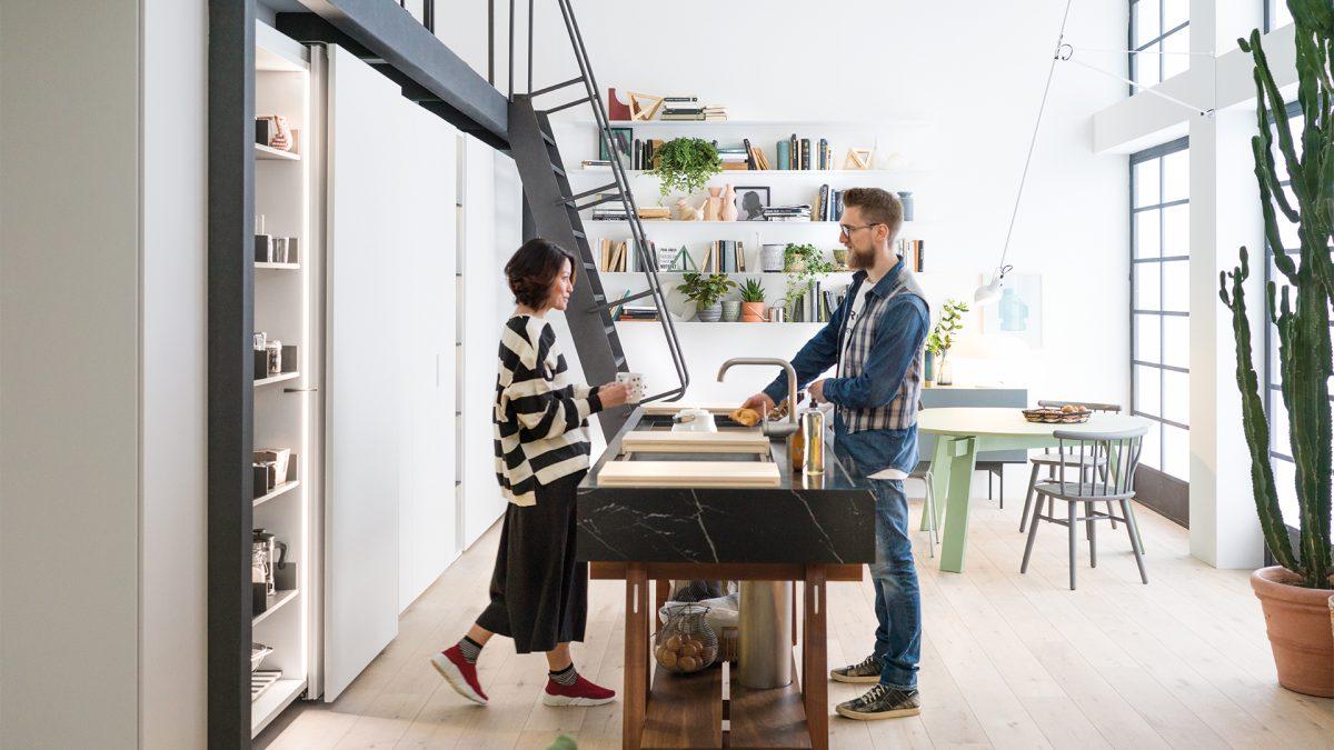 Foto di due persone che chiacchierano in una cucina composta da una parete con il sistema Freedhome