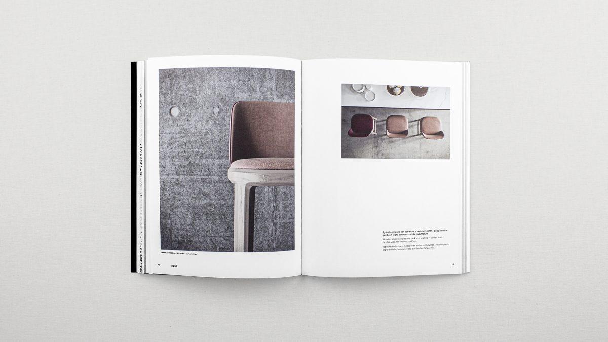 Foto del catalogo aperto che mostra le pagine inerenti allo sgabello Damblé con breve testo e due render dello sgabello, uno zenitale e uno di dettaglio del prodotto