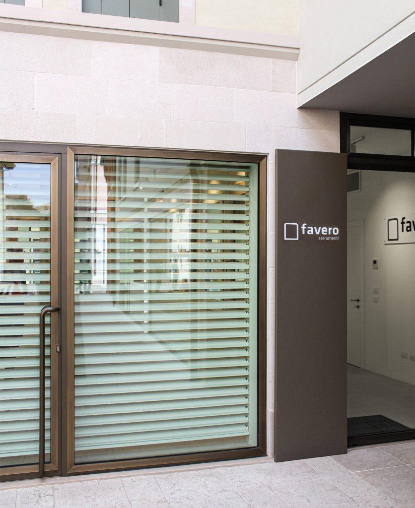 vista di scorcio dell'ingresso del negozio, vetrina sulla sinistra, porta a destra e totem con logo al centro