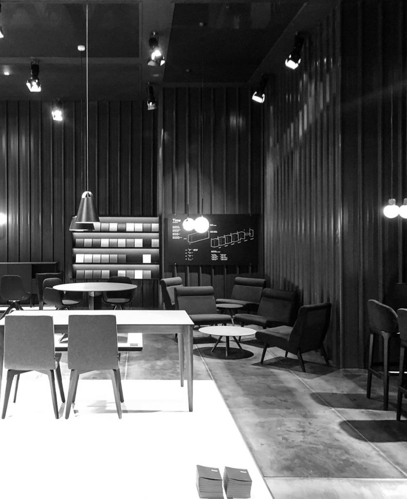 Foto in bianco e nero dello stand con la materioteca e un'infografica dei moduli che compongono le madie