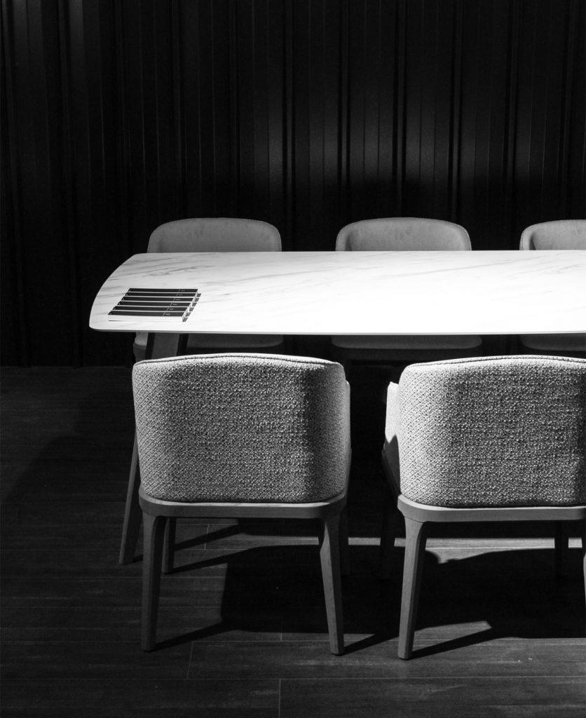 Foto di dettaglio del tavolo Prado e delle poltrone Damblè in bianco e nero