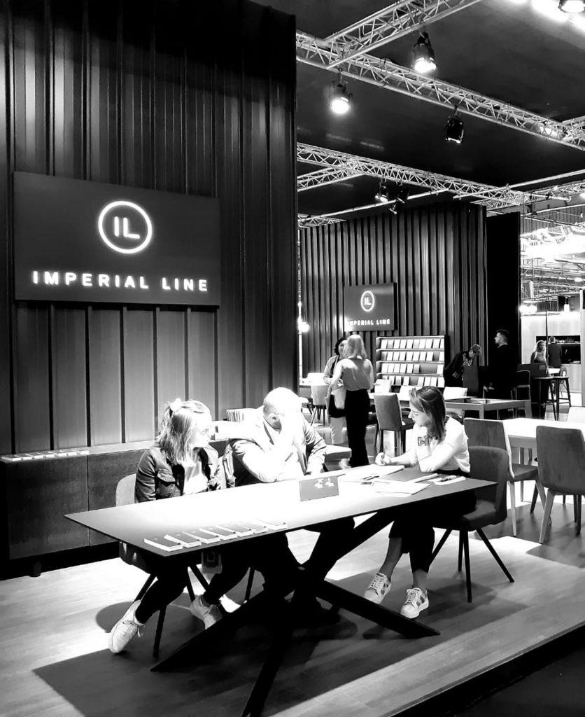 Foto dello stand del salone milano 2019 con all'interno persone che provano i prodotti