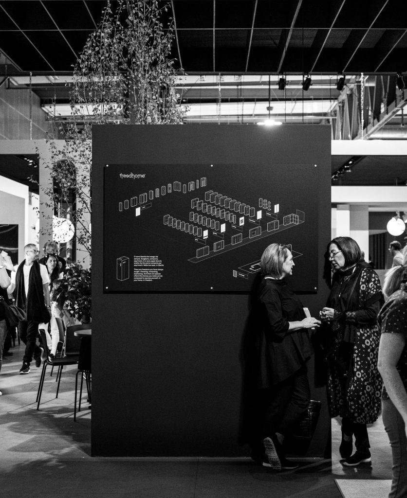 Foto di due donne che parlano di fronte alla grafica a muro che mostra i moduli del sistema freddhome all'interno dello stand del salone
