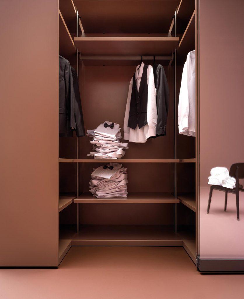 foto di dettaglio di armadio aperto di colore rosso mattone su un ambiente anch'esso color rosso mattone