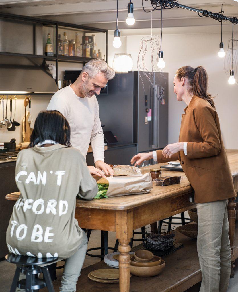 Foto della famiglia riunita in cucina intenta a preparare il pranzo sopra un tavolo in legno