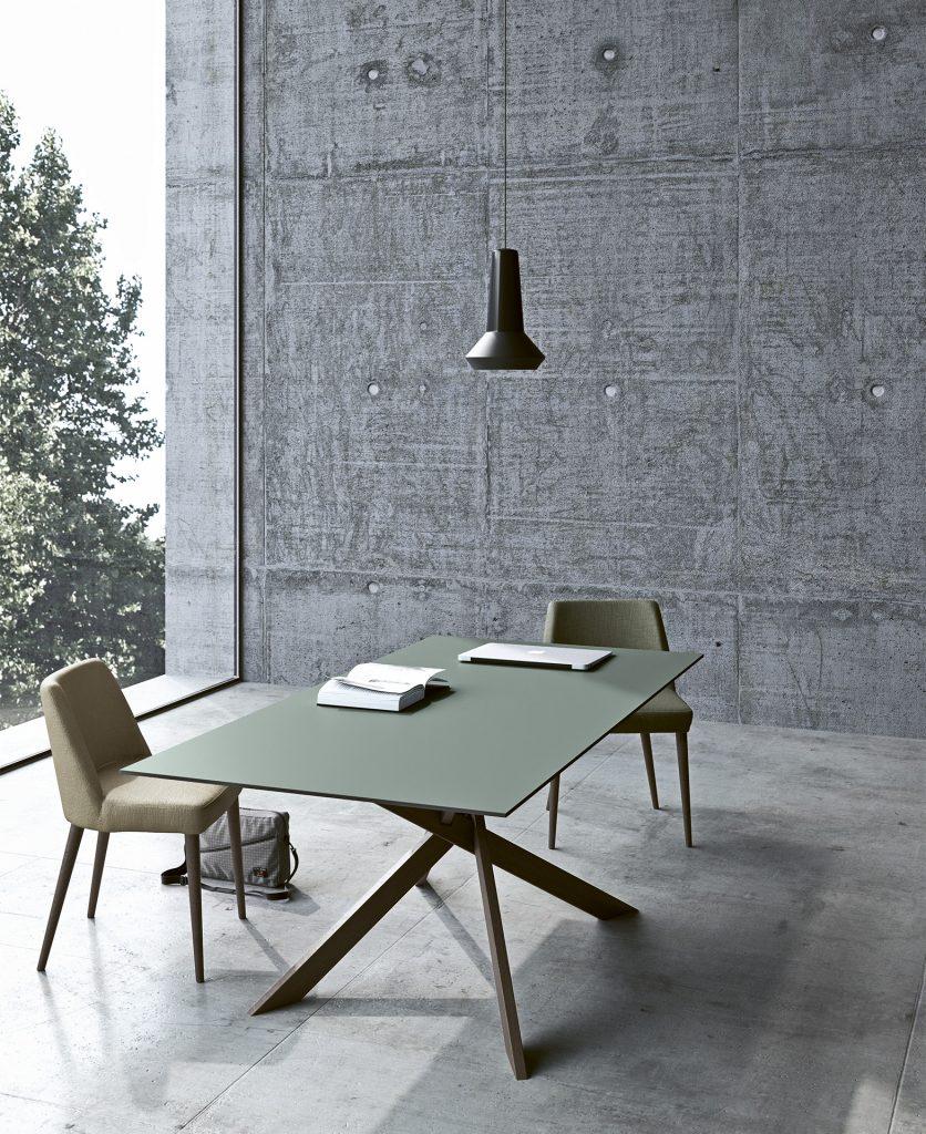 Render del tavolo Maxxi, con al di sopra un pc e un libro, all'interno di un ambiente in cemento grezzo con due sedie fenice attorno