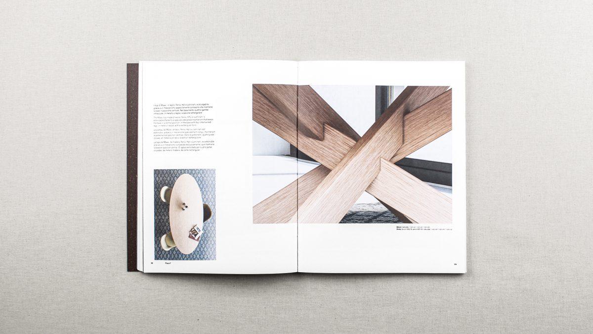 Foto delle pagine del catalogo riguardanti il tavolo Maxxi con un testo descrittivo, e due render, una vista zenitale del tavolo e una vista di dettaglio dell'incrocio delle gambe