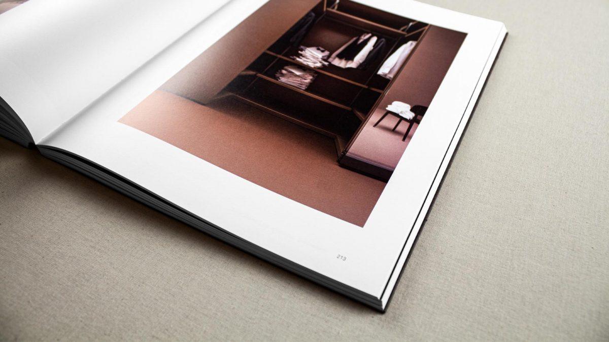 vista di scorcio del catalogo aperto dove si vede l'immagine di un armadio colore rosso mattone su un ambiente anch'esso color rosso mattone