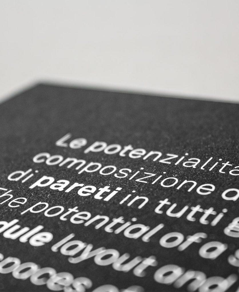 vista di scorcio del retro della brochure dove si vede una parte di un testo emozionale