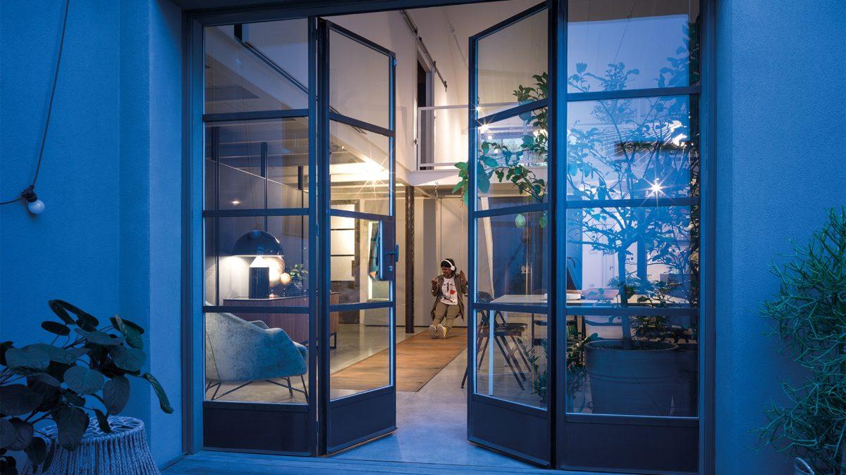 Foto dell'esterno dell'abitazione con la porta vetrata aperta a mostrare il soggiorno