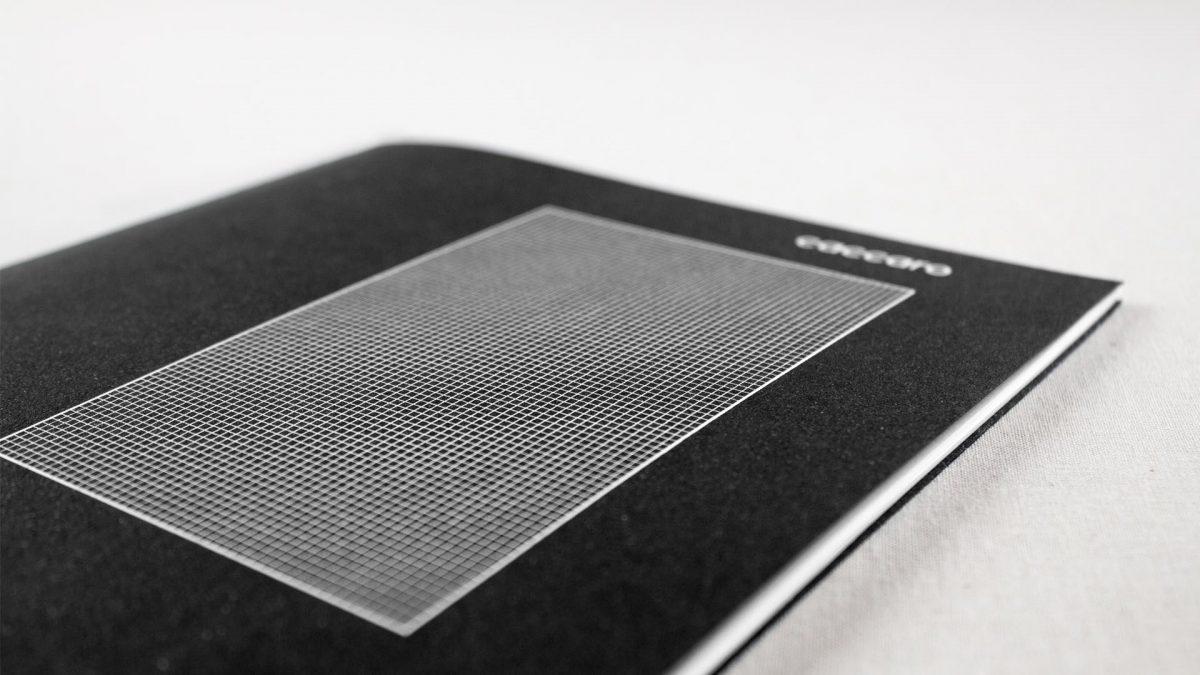 vista di scorcio della brochure dove si vede il dettaglio della copertina materica nera e con la griglia millimetrata bianca