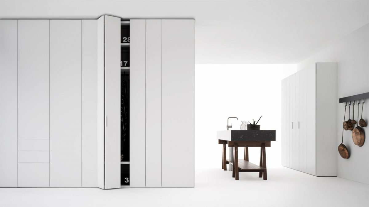 foto emozionale di due armadi entrambi di colore bianco su un ambiente anch'esso color bianco, con una cucina installata in mezzo ai due