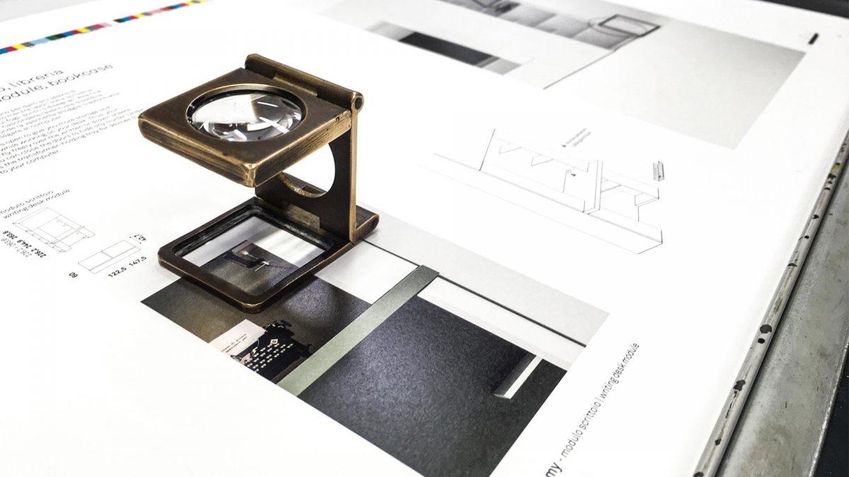 foto emozionale di una prova di stampa fatta dallo stampatore con il dettaglio di una lente posizionata sopra al foglio