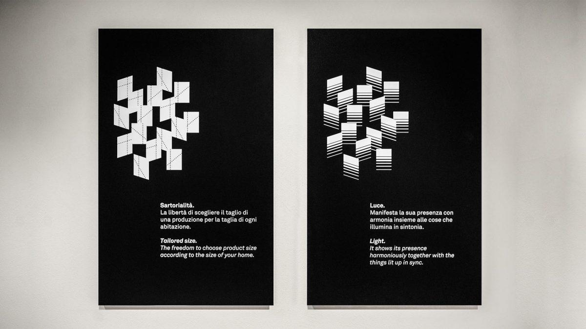Foto delle grafiche appese al flagship store che descrivono la sartorialità e la luce.