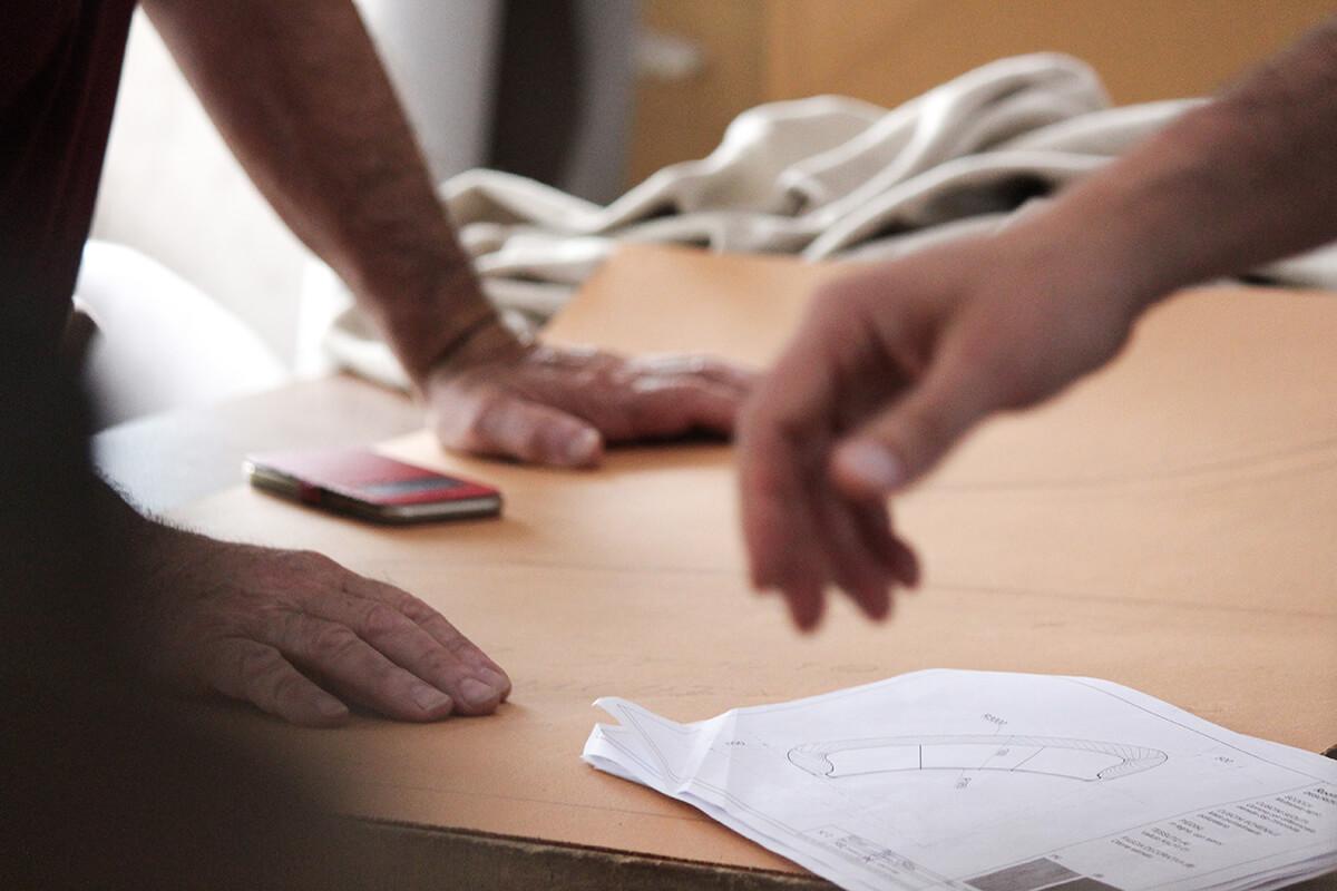 Foto di mani poggiate sopra un tavolo con materiali per la produzione di un divano